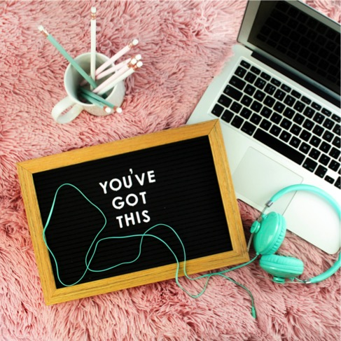 Laptop with headphones and pencils and encouraging note